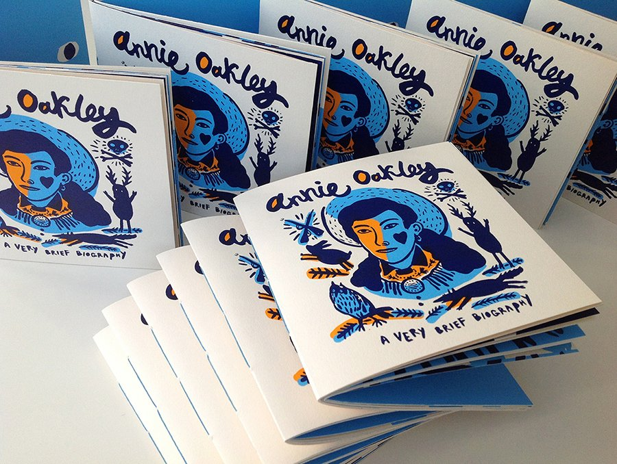 A white leaflet about Annie Oakley with original artwork of her on cover.