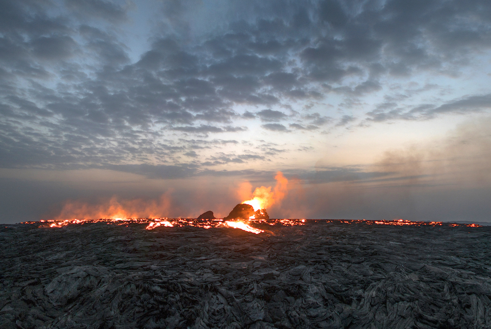 """<p """"="""""""">A photograph of a blackened lava field, with an eruption in progress and fires and molten rock along the horizon line."""