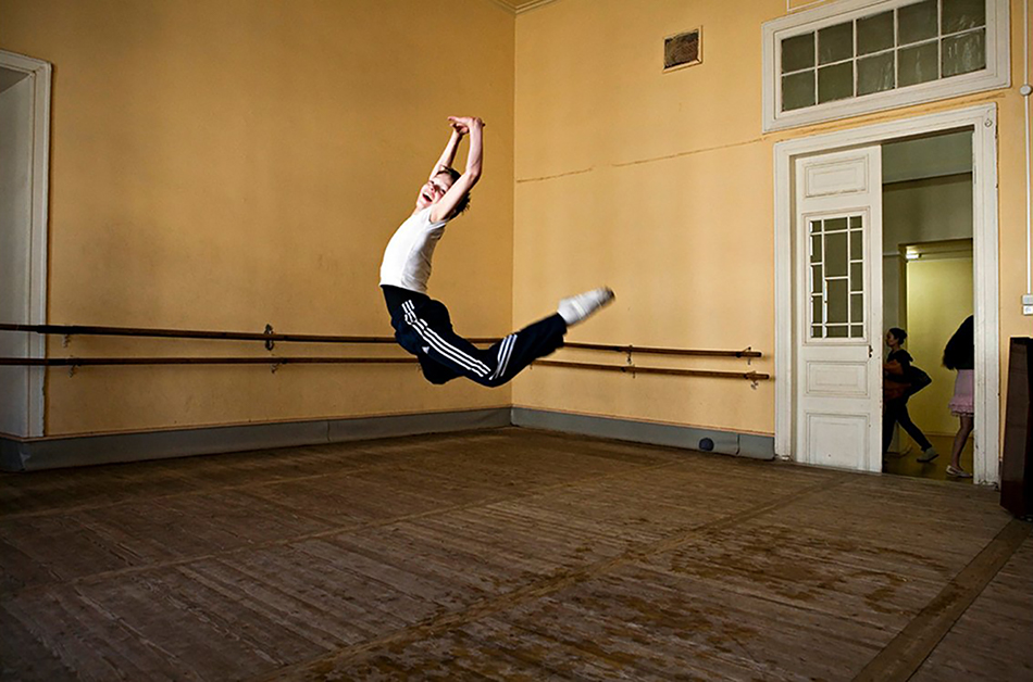 "<p ""="""">A color photograph of a boy smiling and leaping in a dance studio."