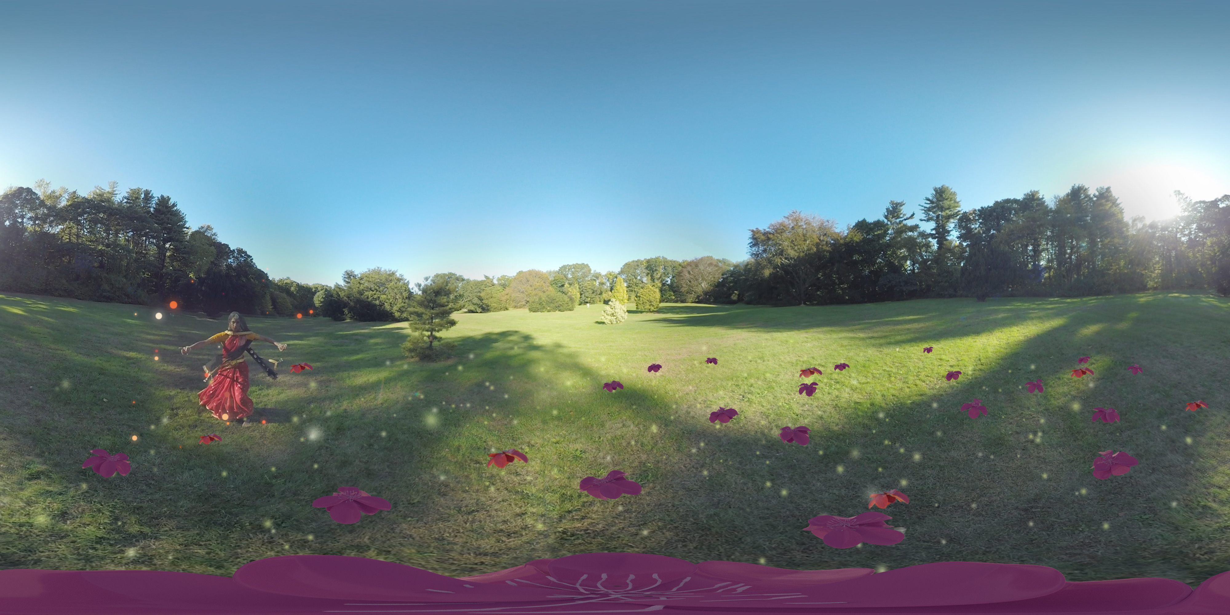 A woman in a red dress dances in a large green field with pink flowers on the grass. There is a bright blue sky and the image is somewhat distorted, since it is a 360 film to be watched with a virtual reality headset.