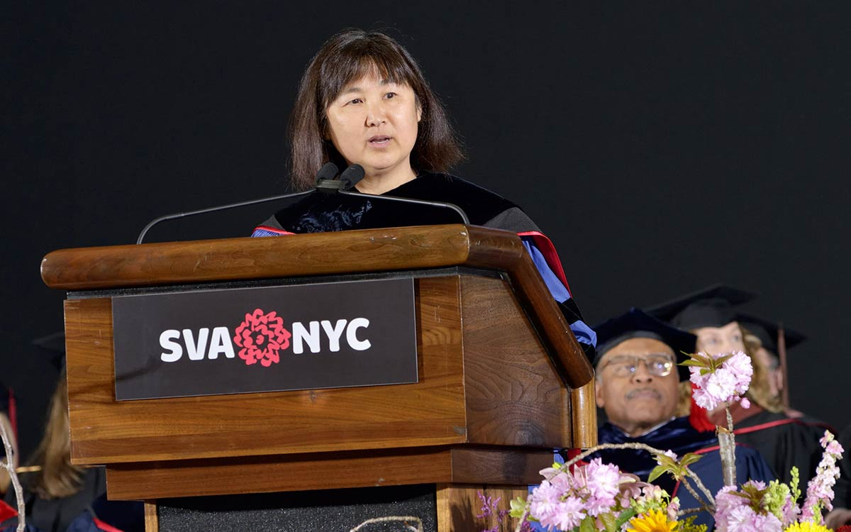 A woman speaks at a podium at a graduation ceremony.
