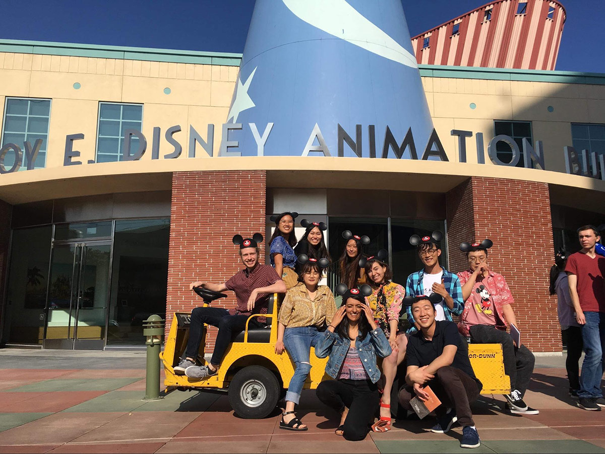 people posing for group photo outside Disney Animation Studio wearing Micky Mouse hats