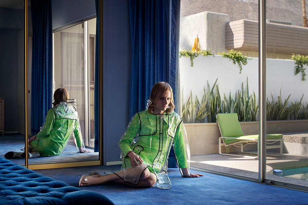 """<p """"="""""""">A photograph of a person in a green dress and clear plastic raincoat, sitting on the floor next to a glass door looking out onto a swimming pool."""