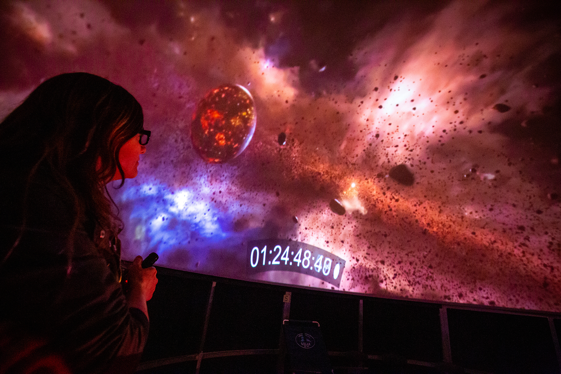 """<p """"="""""""">A woman stands in the foreground, looking at a detailed computer animation of an outer-space scene."""
