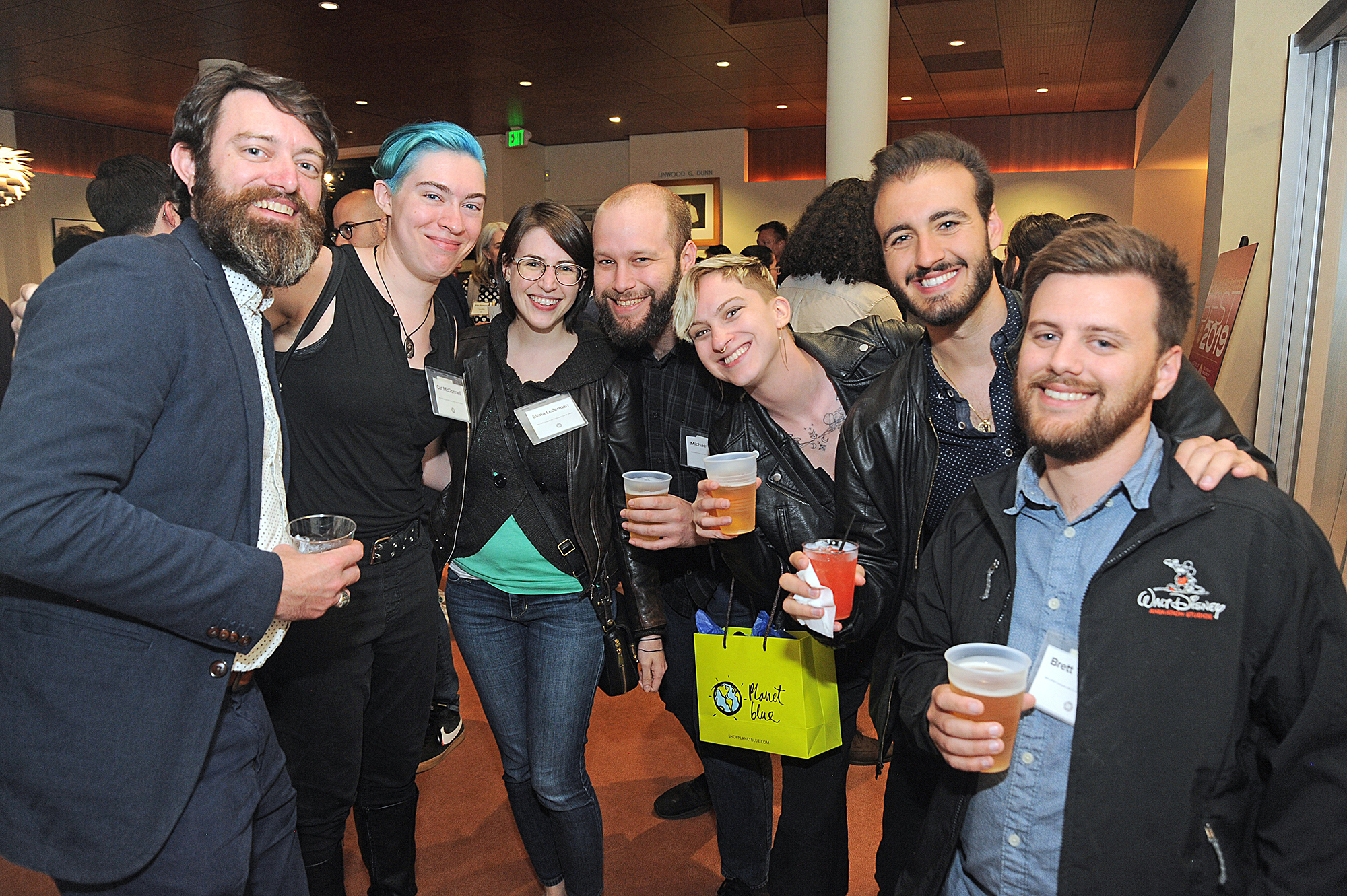 """<p """"="""""""">A group of people at a reception in a movie theater lobby smile for the camera."""