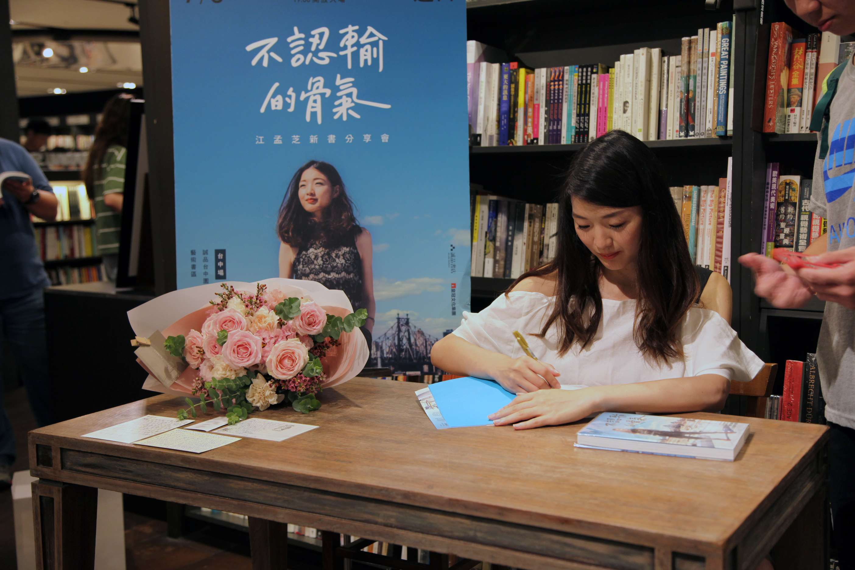 MengChih sitting on a table signing a copy of her book in a bookstore.