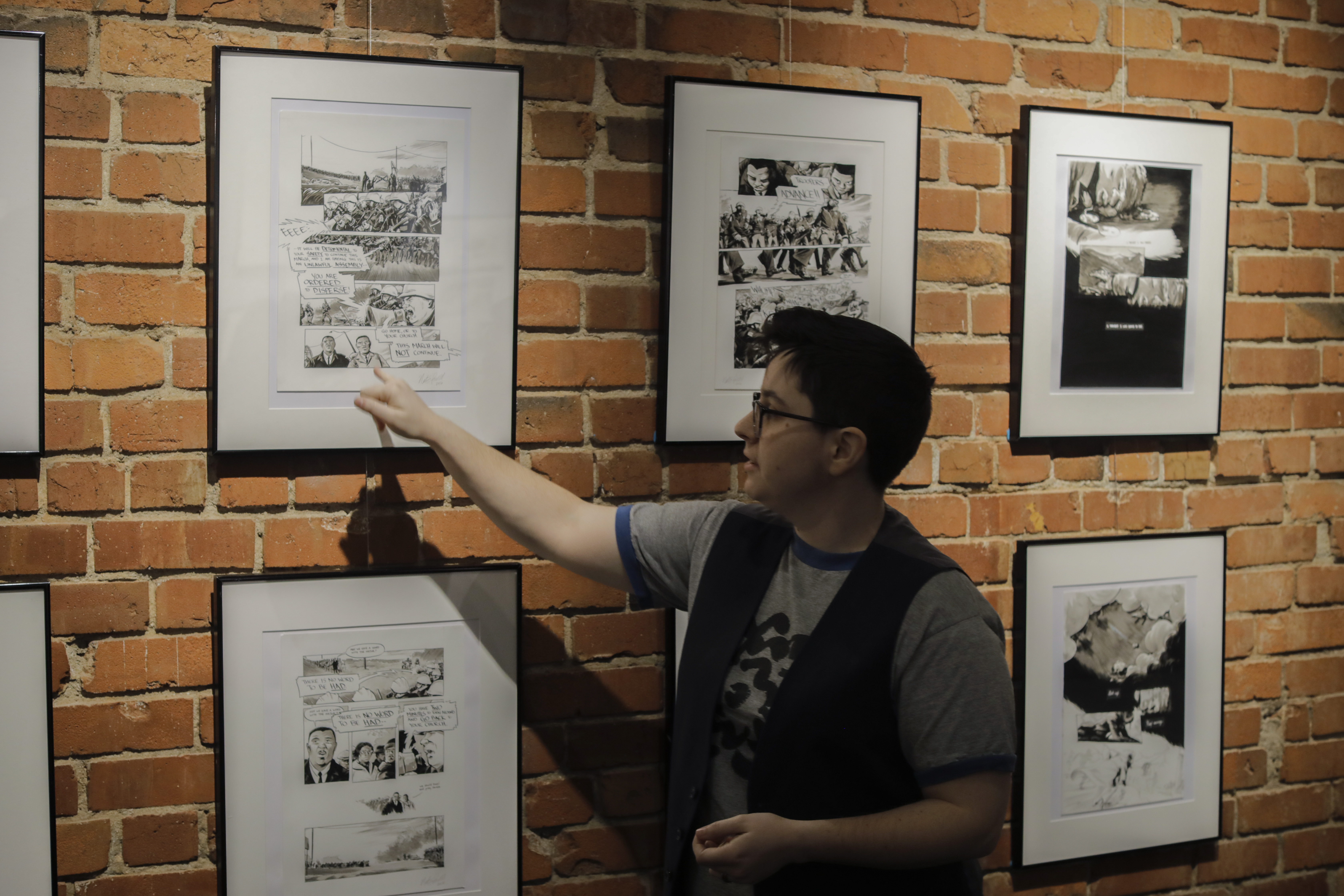 A man pointing to a picture on the brick wall.