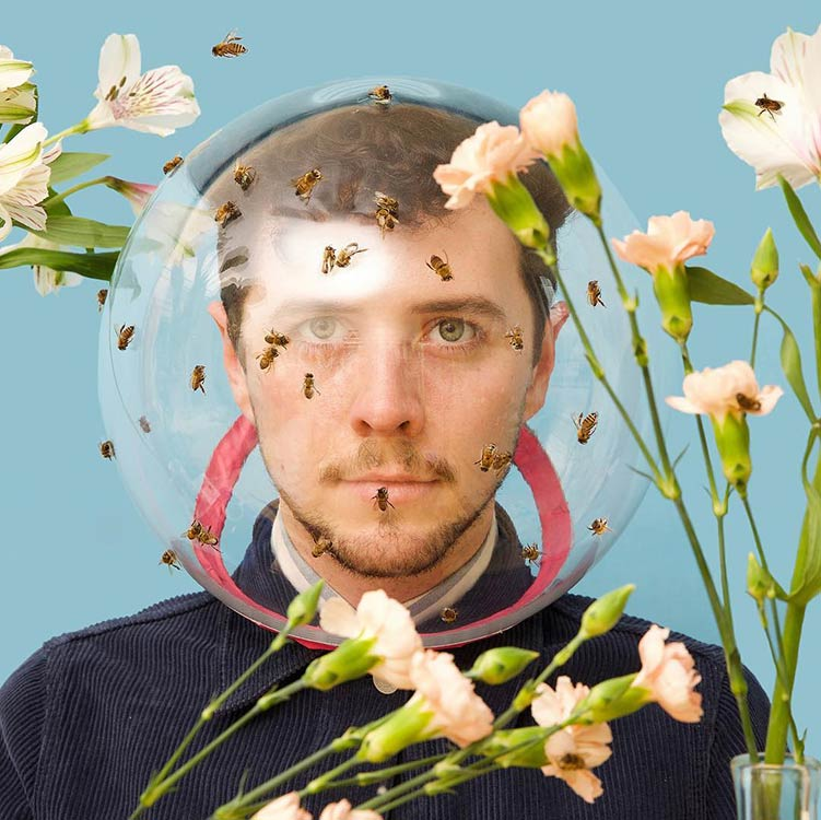 """<p """"="""""""">A man surrounded by bees and flowers wears a protective glass helmet."""