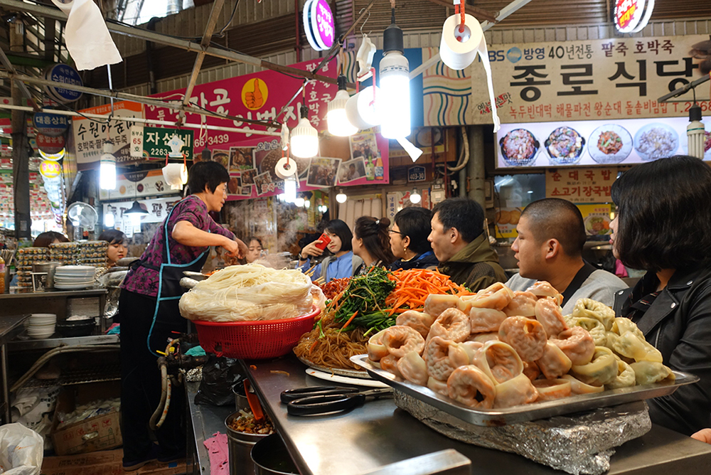 An image of seven people watching a woman cook behind a counter in South Korea.