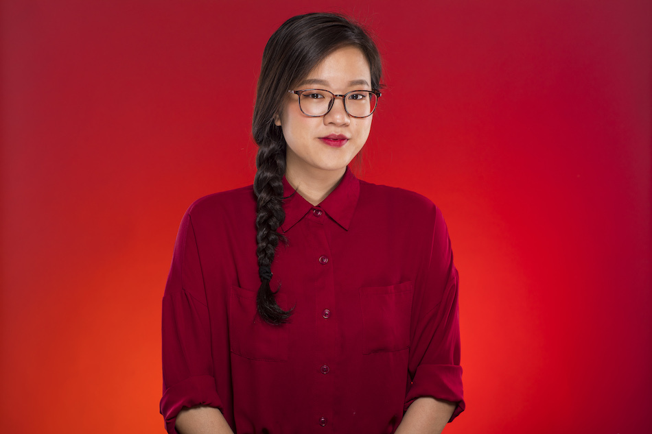 """<p """"="""""""">A color photograph of a young woman facing the camera and wearing glasses and a red shirt."""