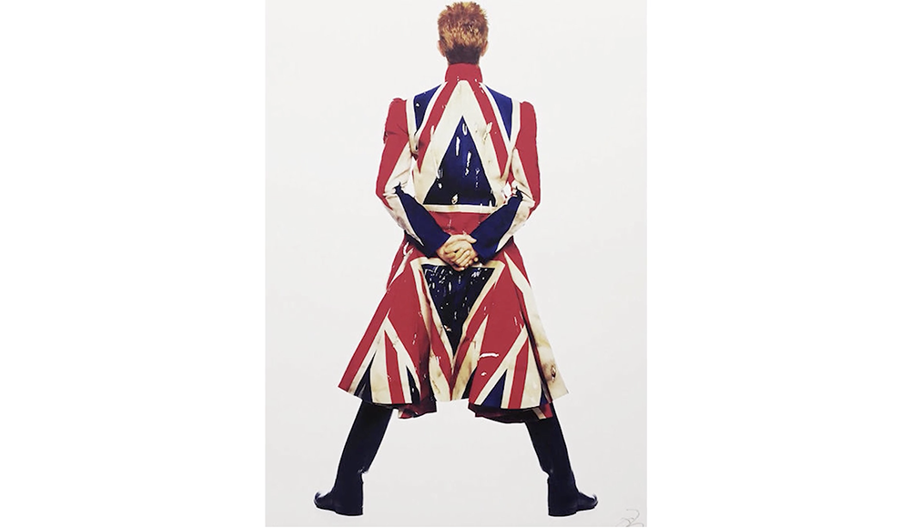 David Bowie from the back wearing a coat made from the British flag.