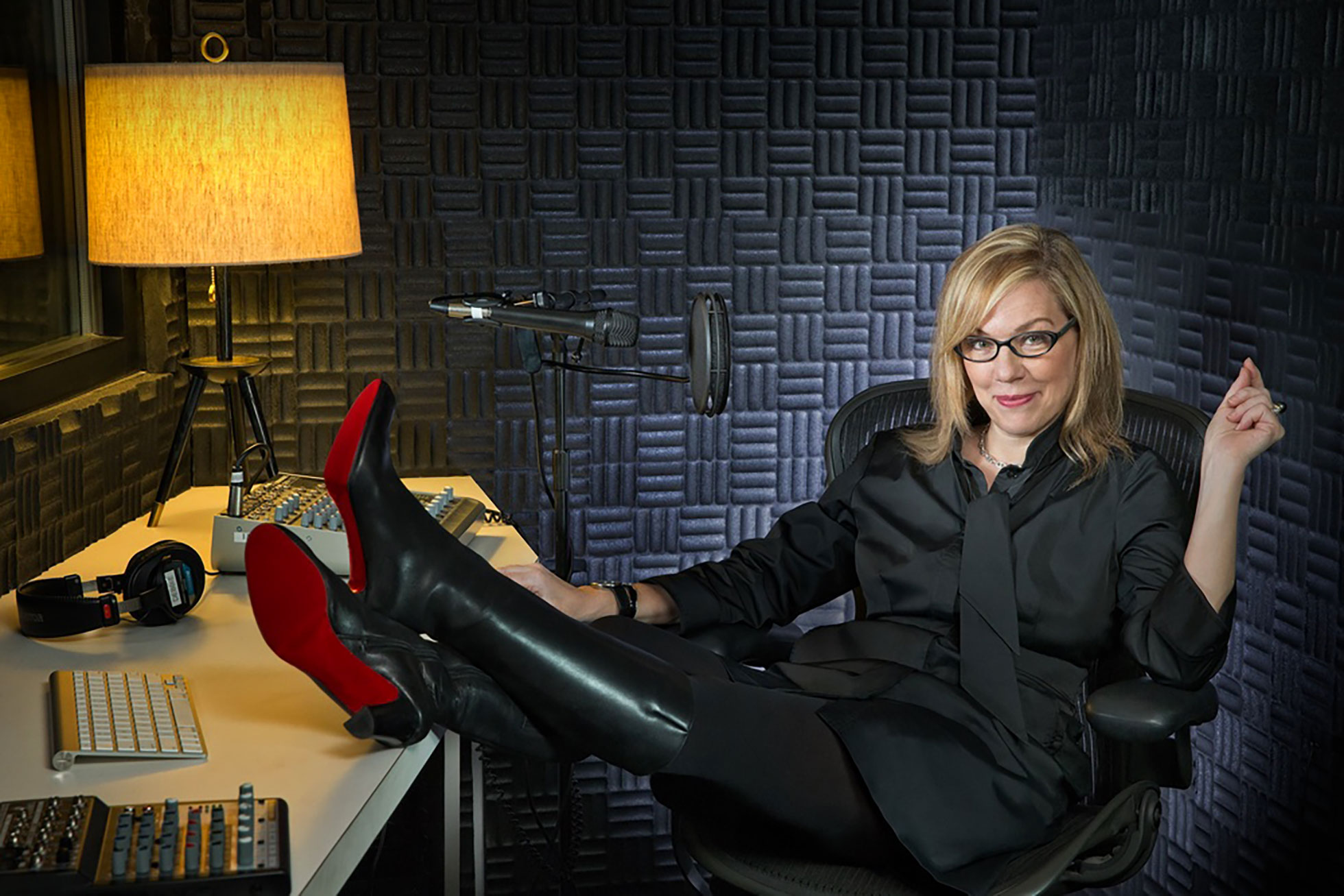 A woman sits in a chair with her feet on the desk inside of a recording studio.