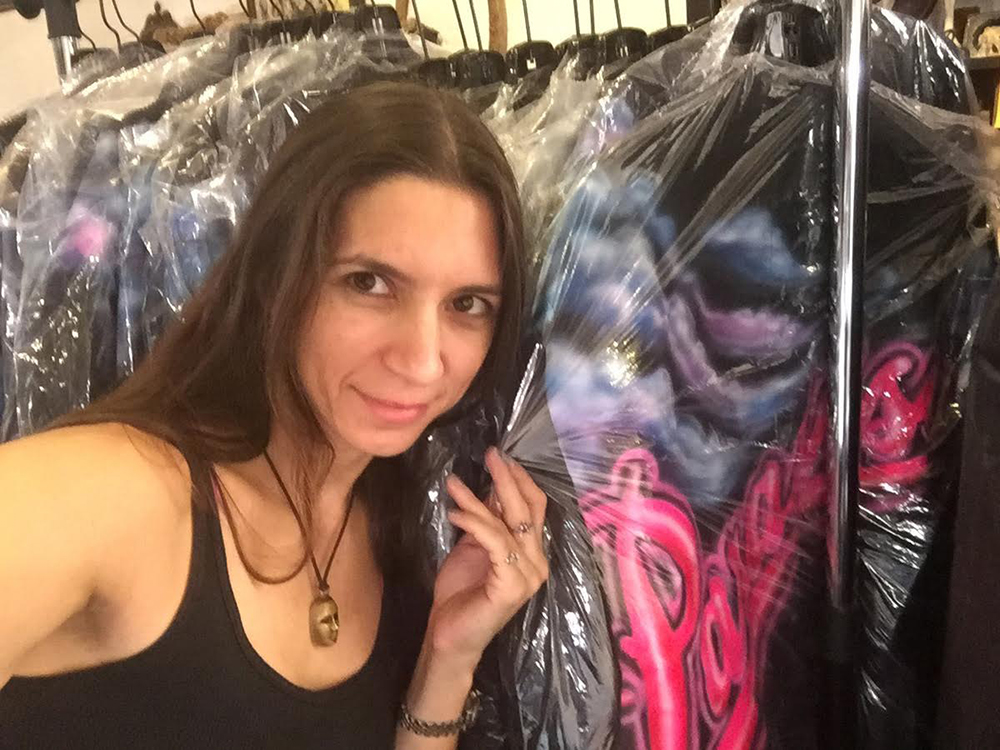 A lady in a black tank top holding plastic that is covering clothes on a rack.