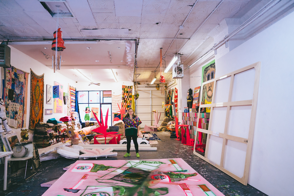 """<p """"="""""""">A woman stands in the middle of an art studio filled with large paintings, hanging and stacked rugs, sculptures, pinatas and other objects."""