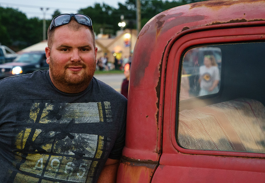 Burly man next to rusty old red truck