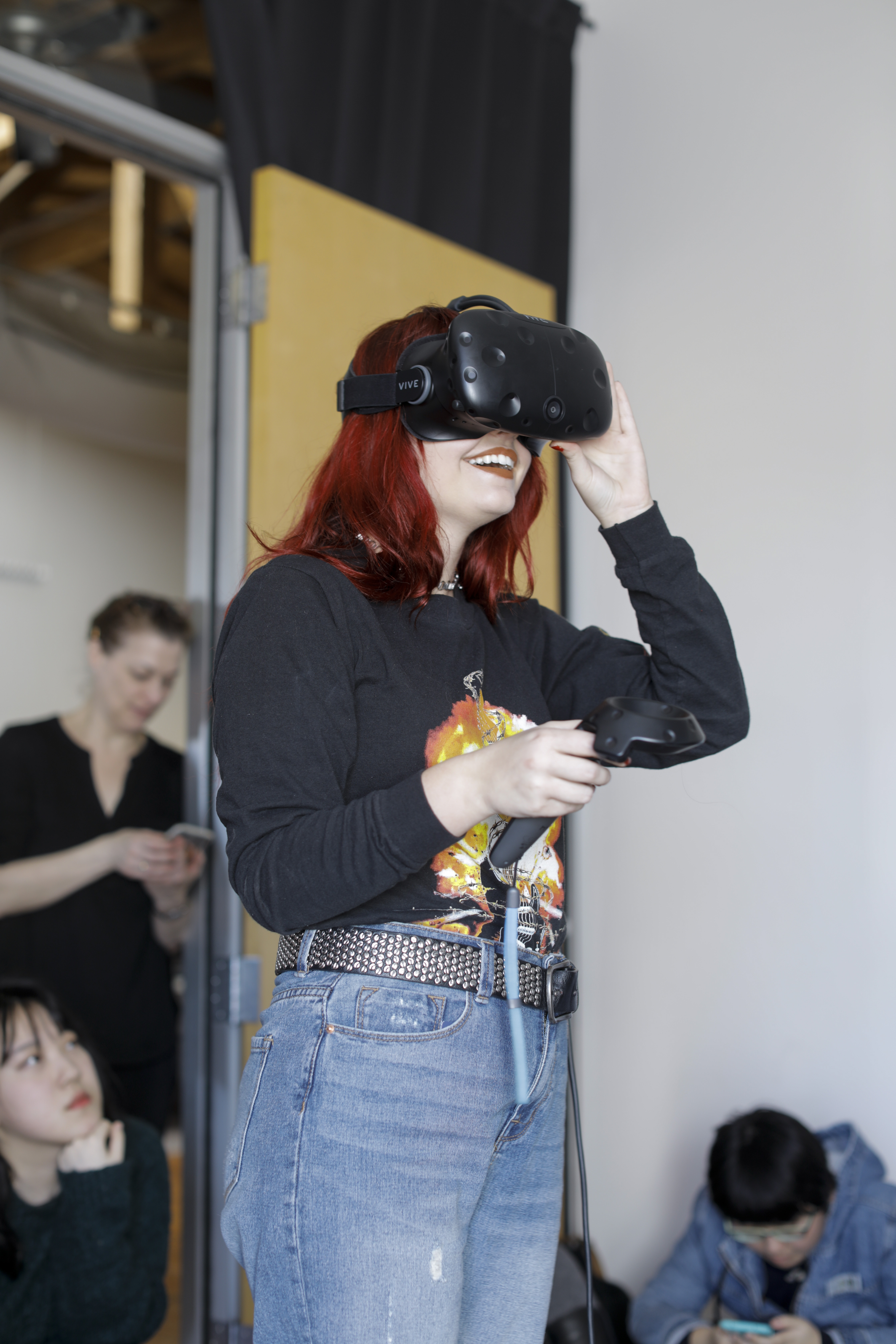 A red-haired woman with a studded belt using a HTC Vive virtual reality headset.