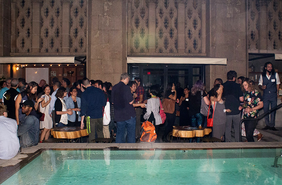 People at a gathering near a pool, conversing and drinking