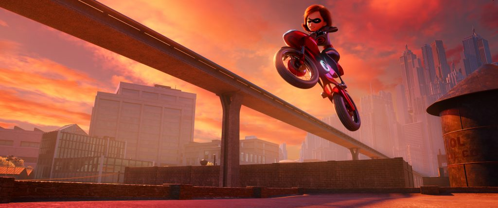 A still from Incredibles 2, of Elastigirl riding a motorcycle with a city backdrop at dusk.