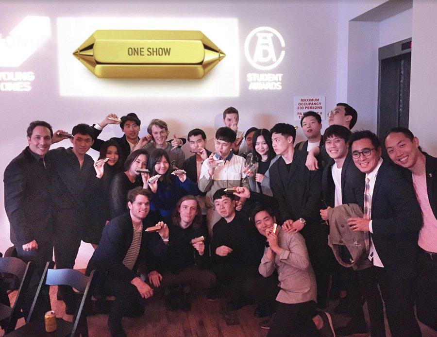 A group photo of people who have won an award. Everyone looks happy and each person is holding a gold item.