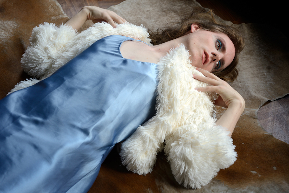 """<p """"="""""""">A photograph of a person lying on the floor, wearing a blue slip dress and white jacket."""