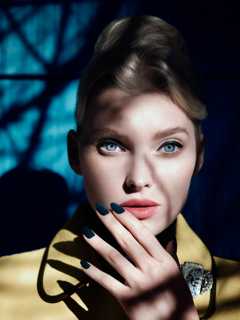 A woman standing in front of a blue background covered in shadows. The woman is pale skinned, has blue eyes, pink lips, blue finger nails, a yellow coat, and light hair. She is holding her hand to her face. She has jewelery on her coat.