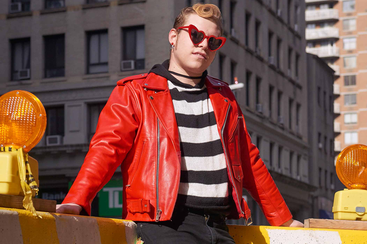 A young man wearing a red leather jacket, black-and-white striped shirt and heart-shaped sunglasses.