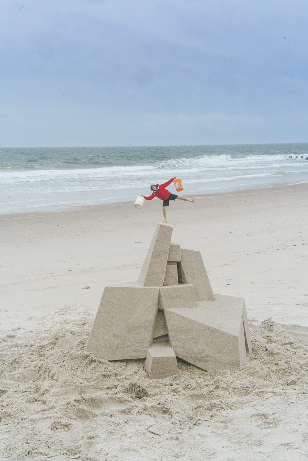 """<p """"="""""""">Seibert poses for a photograph with his sandcastle and buckets."""