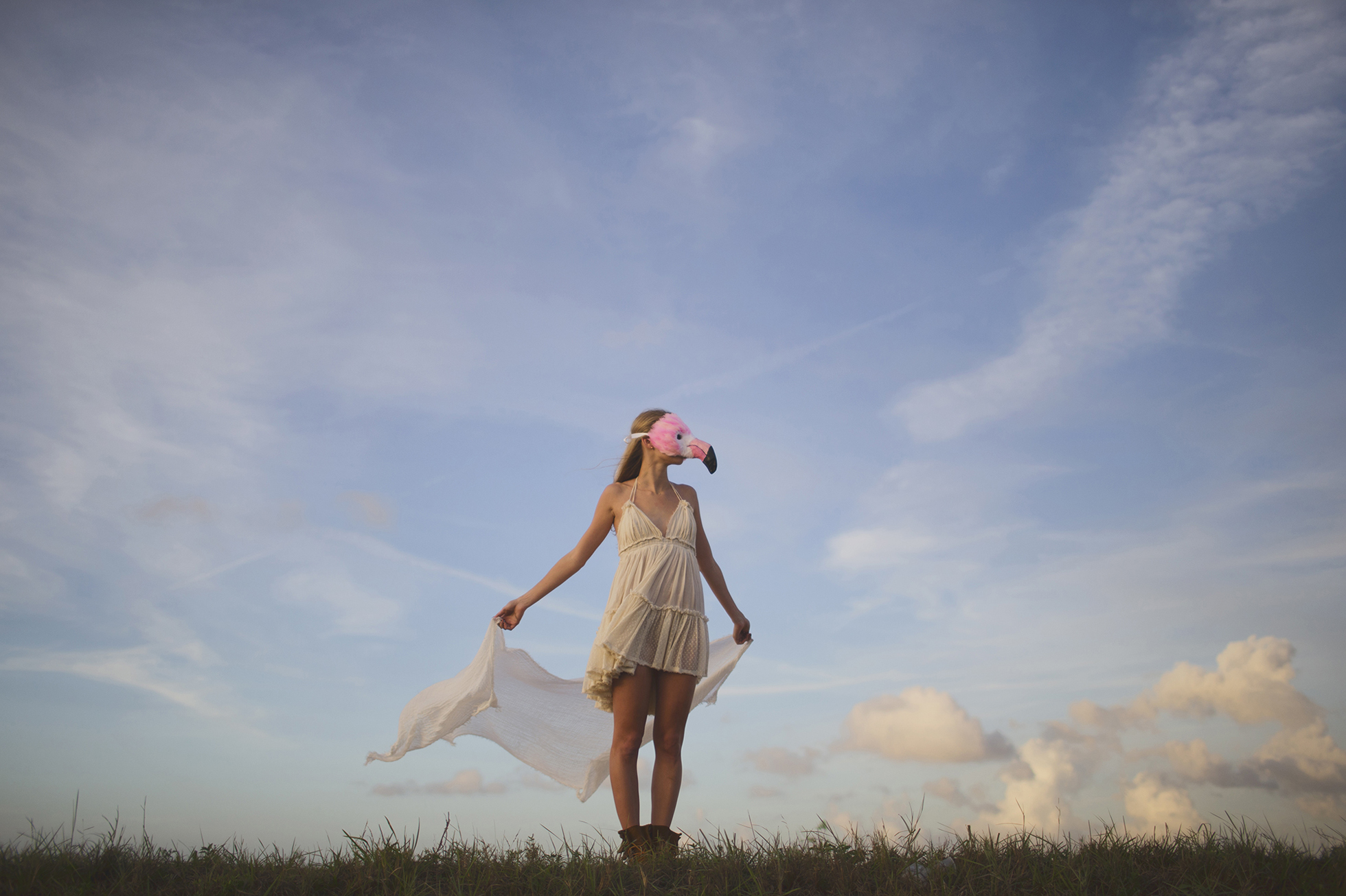 Girl in white dress and flamingo mask
