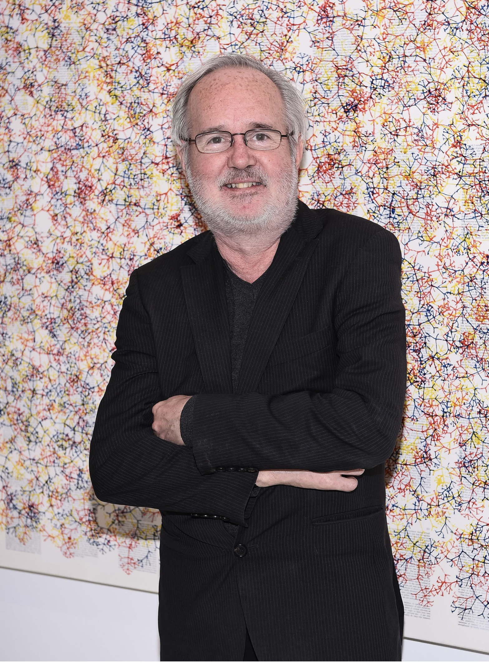 a man leans up against a decorative wall while smiling