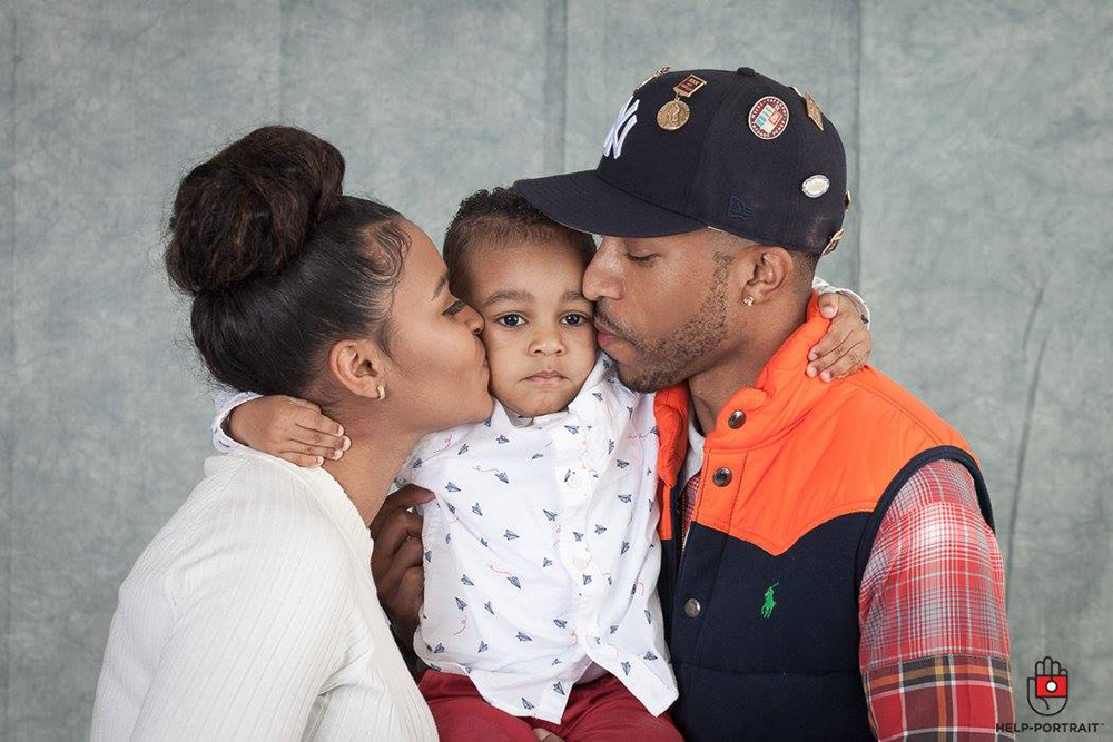 Two parents kissing their child