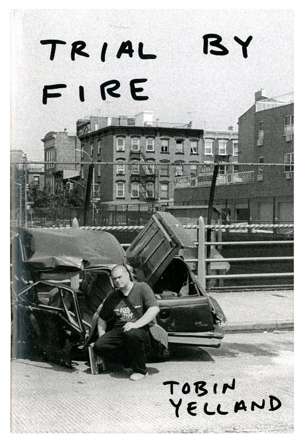 A man in a city squatting in front of a wrecked car