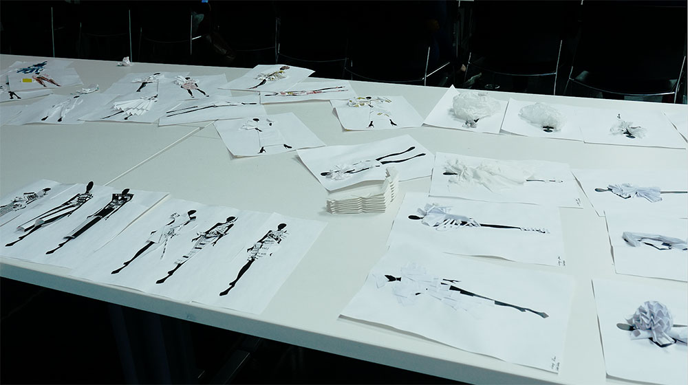 A bunch of paper art laying on a table with black lady figures on them.