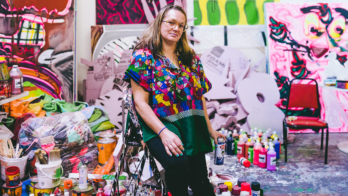 """<p """"="""""""">A woman leans against a stepladder with a can of spray paint in her hand, surrounded by colorful paintings and art supplies."""