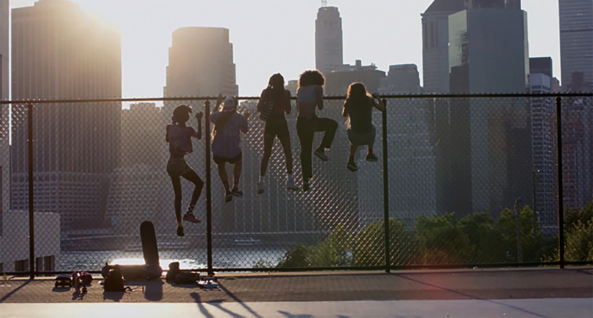 Five skaters scaling a fence in a city