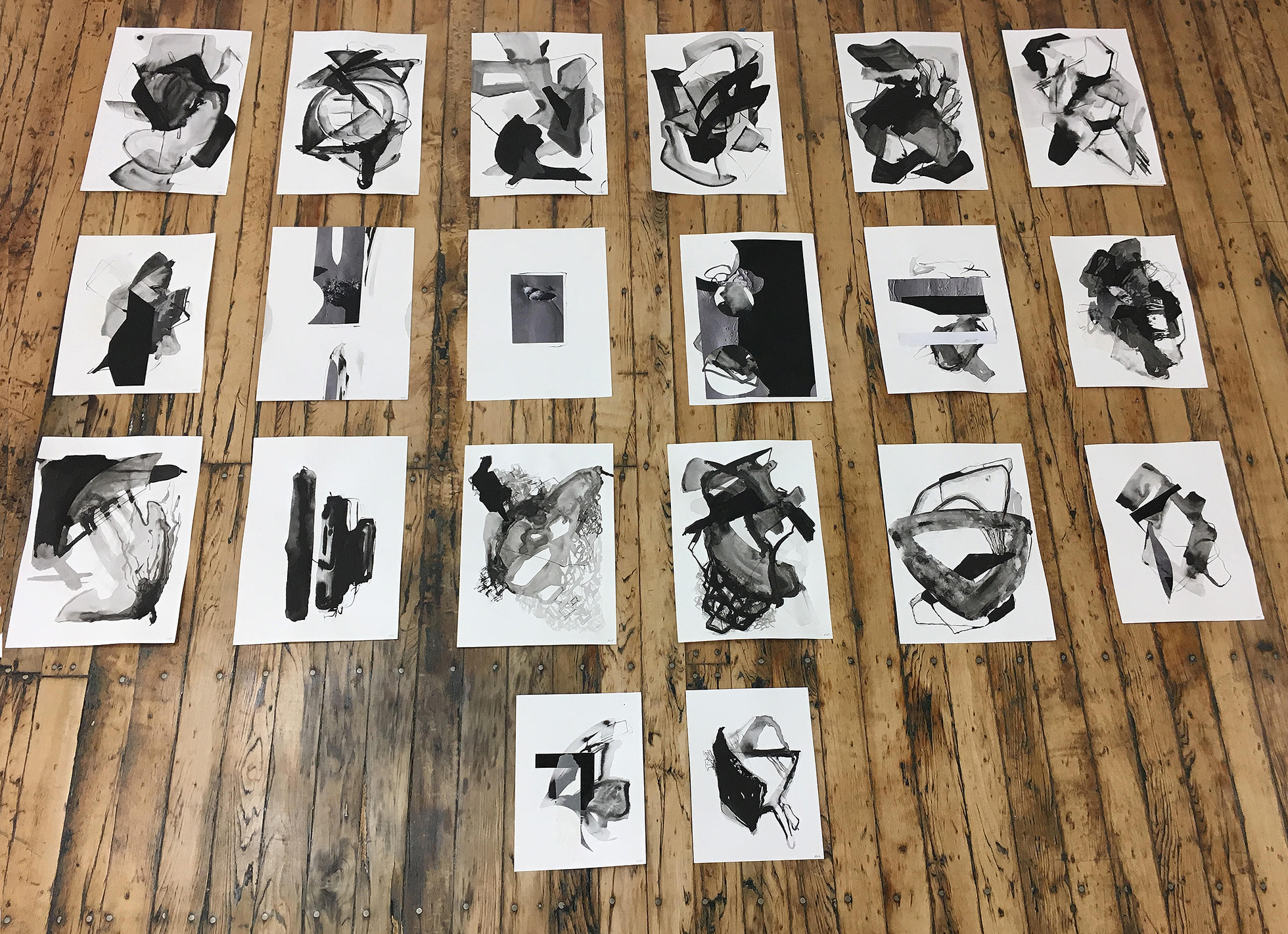 Index cards with abstract images lying on a wooden floor.