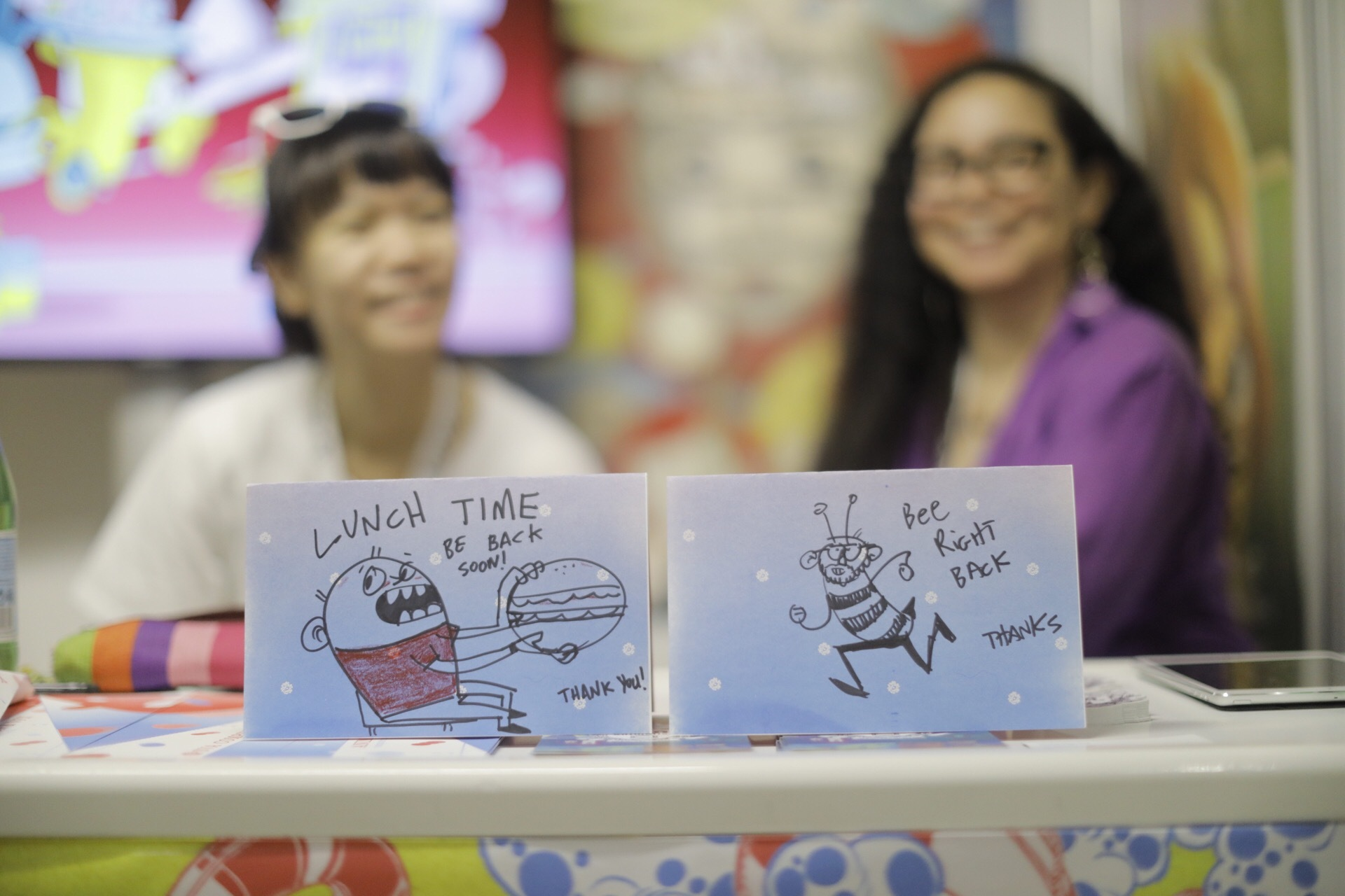 """A photograph of two hand-drawn """"Be back soon""""-type signs propped on a table."""