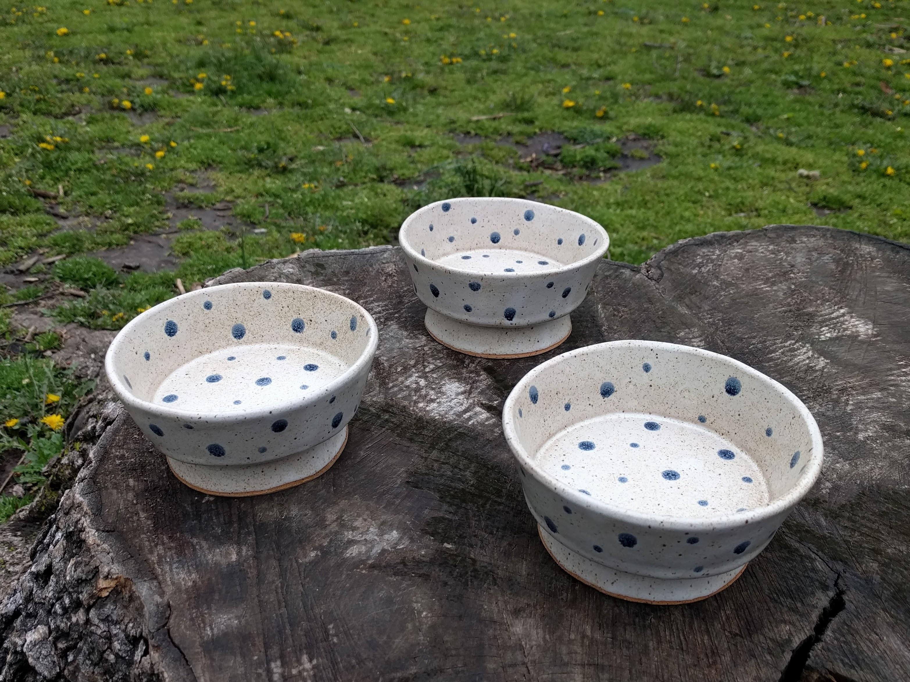 Three speckled bowls sitting on a tree stump.