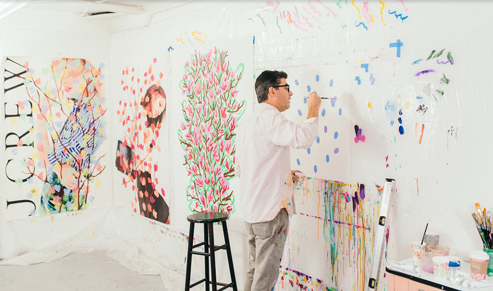 A man painting in a room. The paintings are of J. Crew, two include women, and some have flowers.