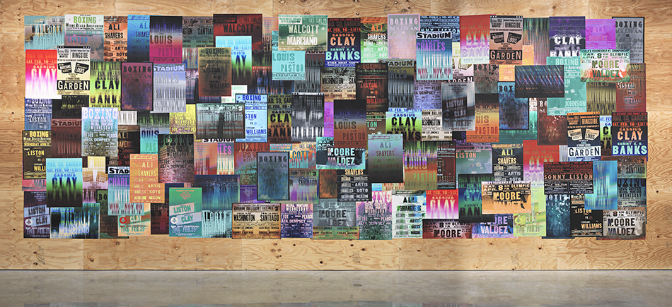 A large-scale collage of colorful, blurry reproductions of boxing posters on a plywood wall.