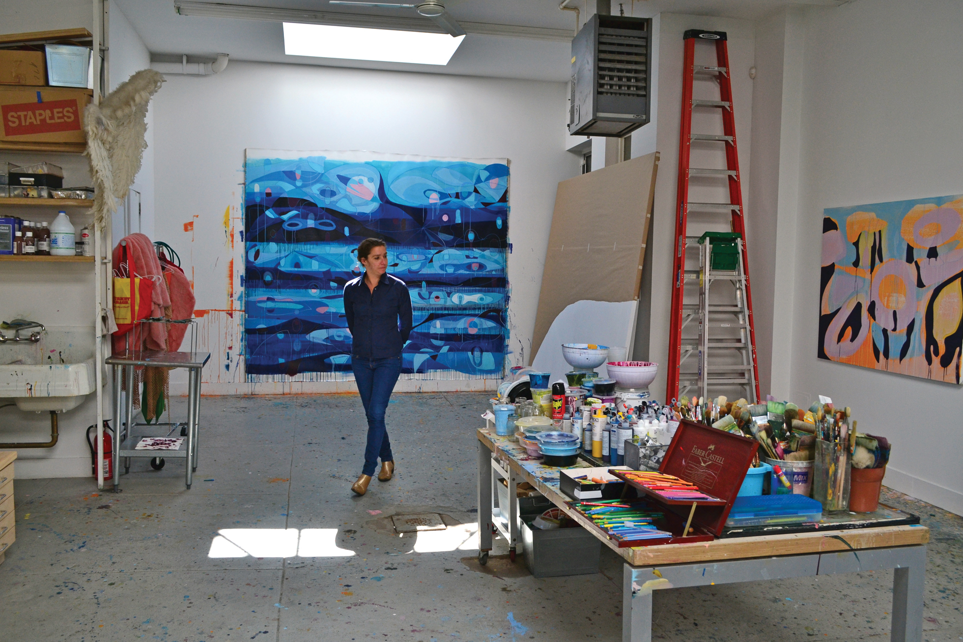 A woman walking through an art studio.