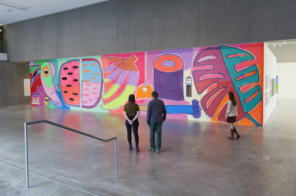 """<p """"="""""""">Three museum visitors are seen from behind as they look at a large, colorful mural featuring a tropical bird, watermelon slices, bananas and other objects."""