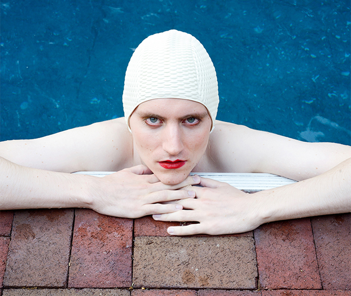 """<p """"="""""""">A photograph of a person in a swimming cap, resting at the edge of a pool."""