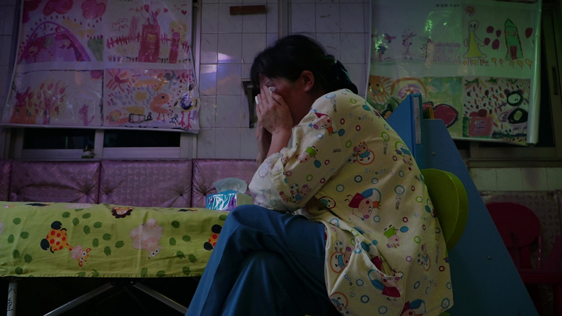 In a tiled room with colorful children's drawings covering the closed windows, a woman presses her hands against her face, crying into a tissue.