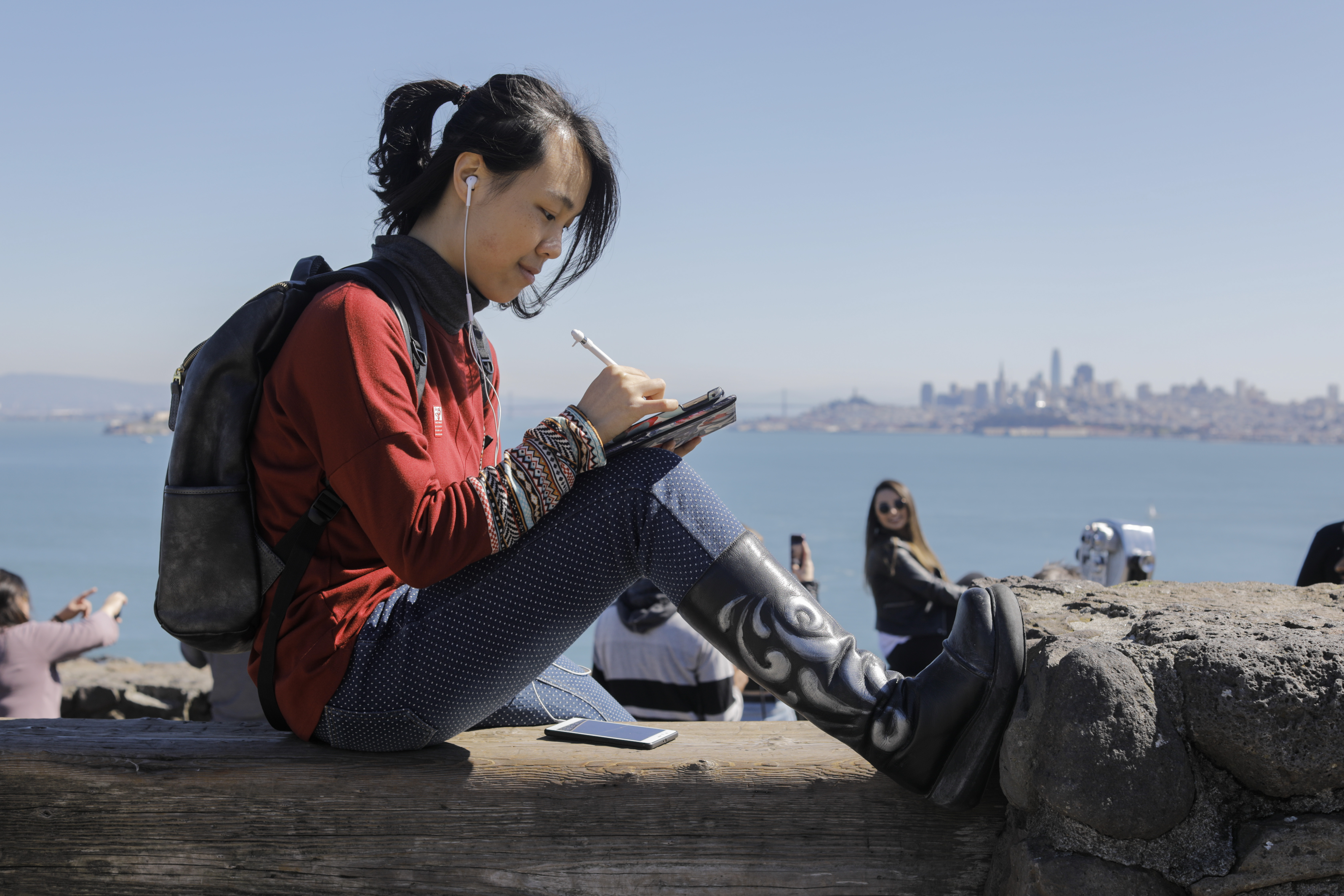 A woman sits in a scenic location and writes on her tablet while listening to music.