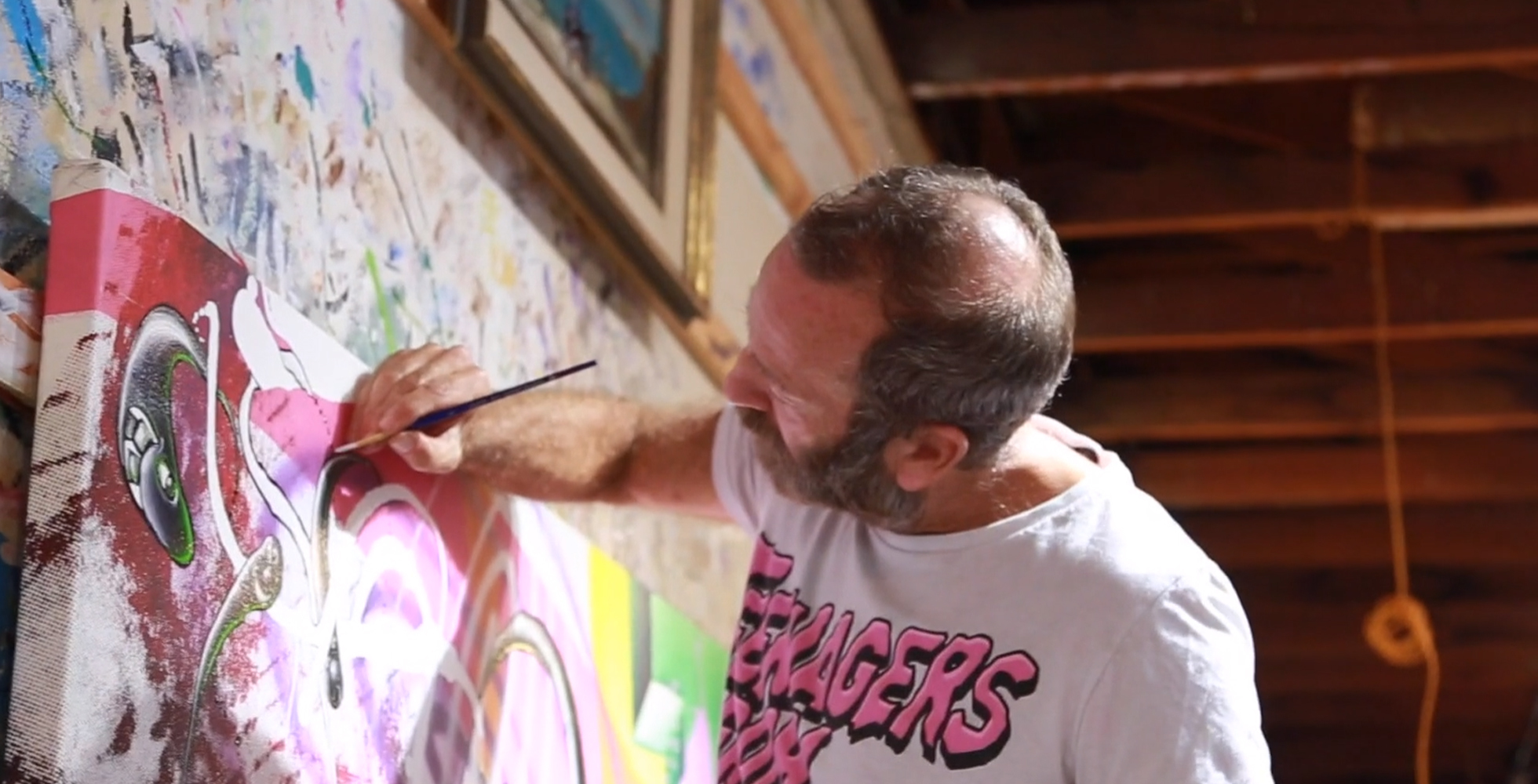 A man painting on a canvas.