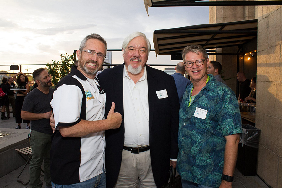 Three men smiling at party. One friend giving a thumbs up.