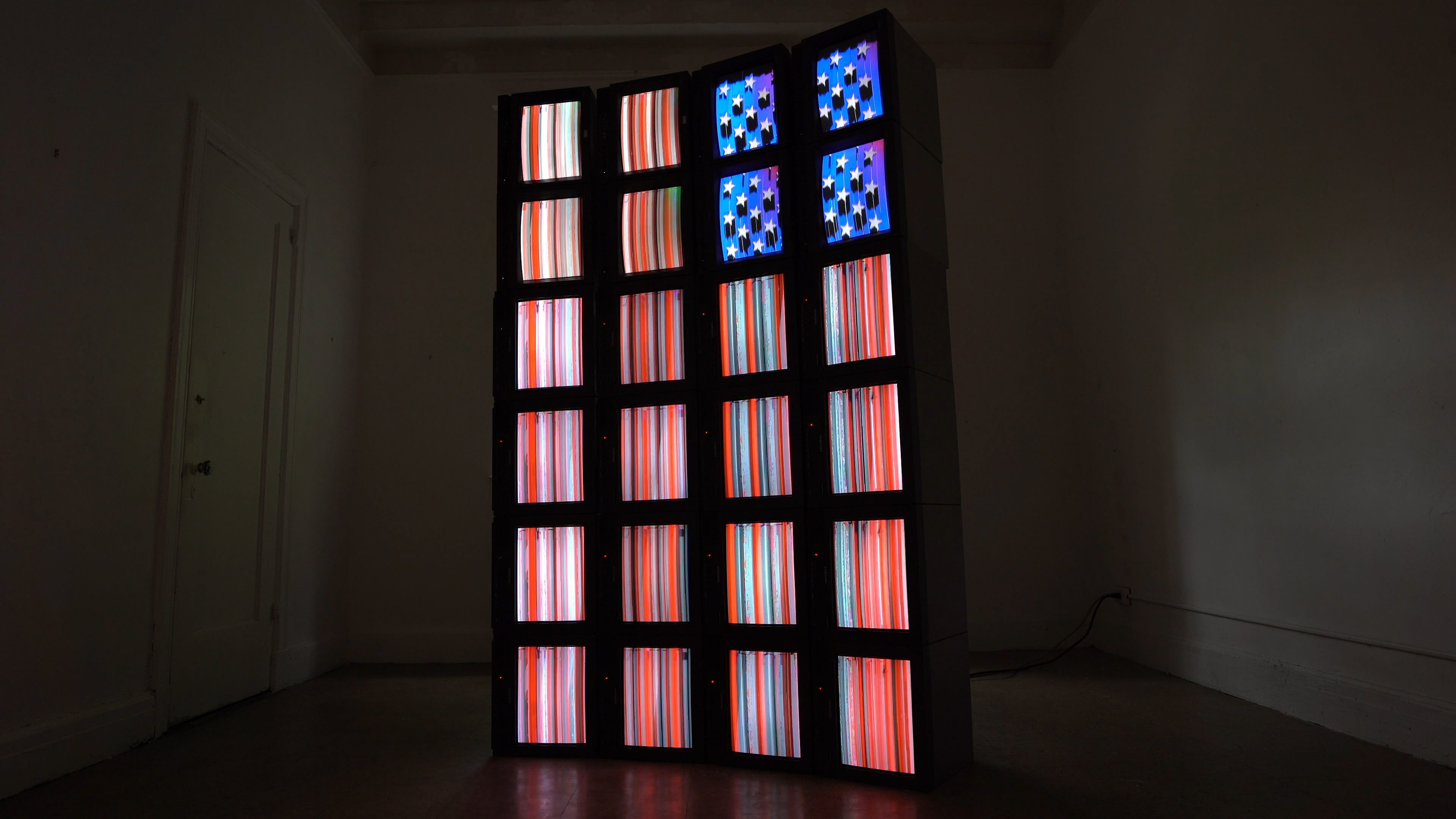 Video sculpture of 24 televisions stacked on top of each other resembling the American flag