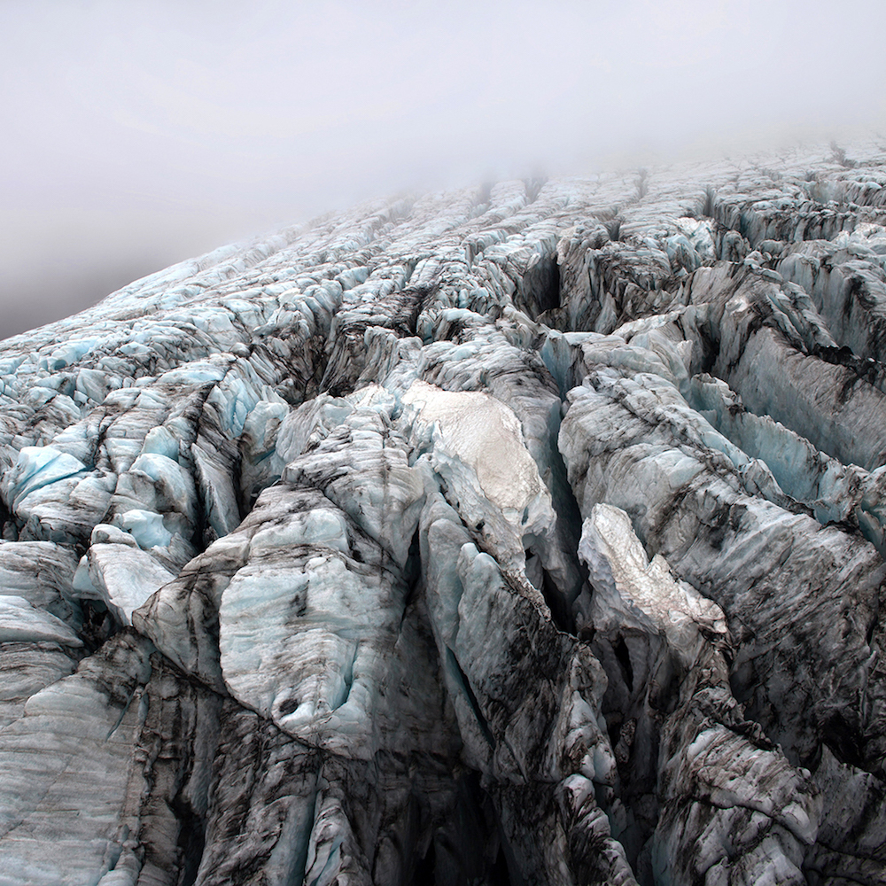 """<p """"="""""""">A photograph of the serrated surface of a glacier emerging from a fog."""
