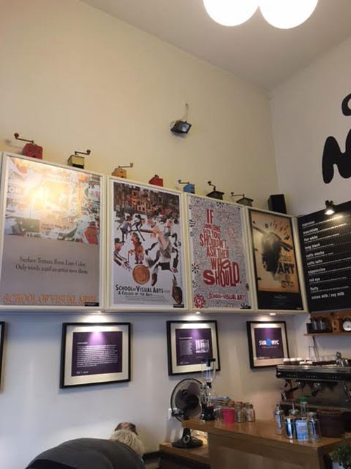 A room filled with wall art posters.  There is also a desk with a fan and a few drinks.