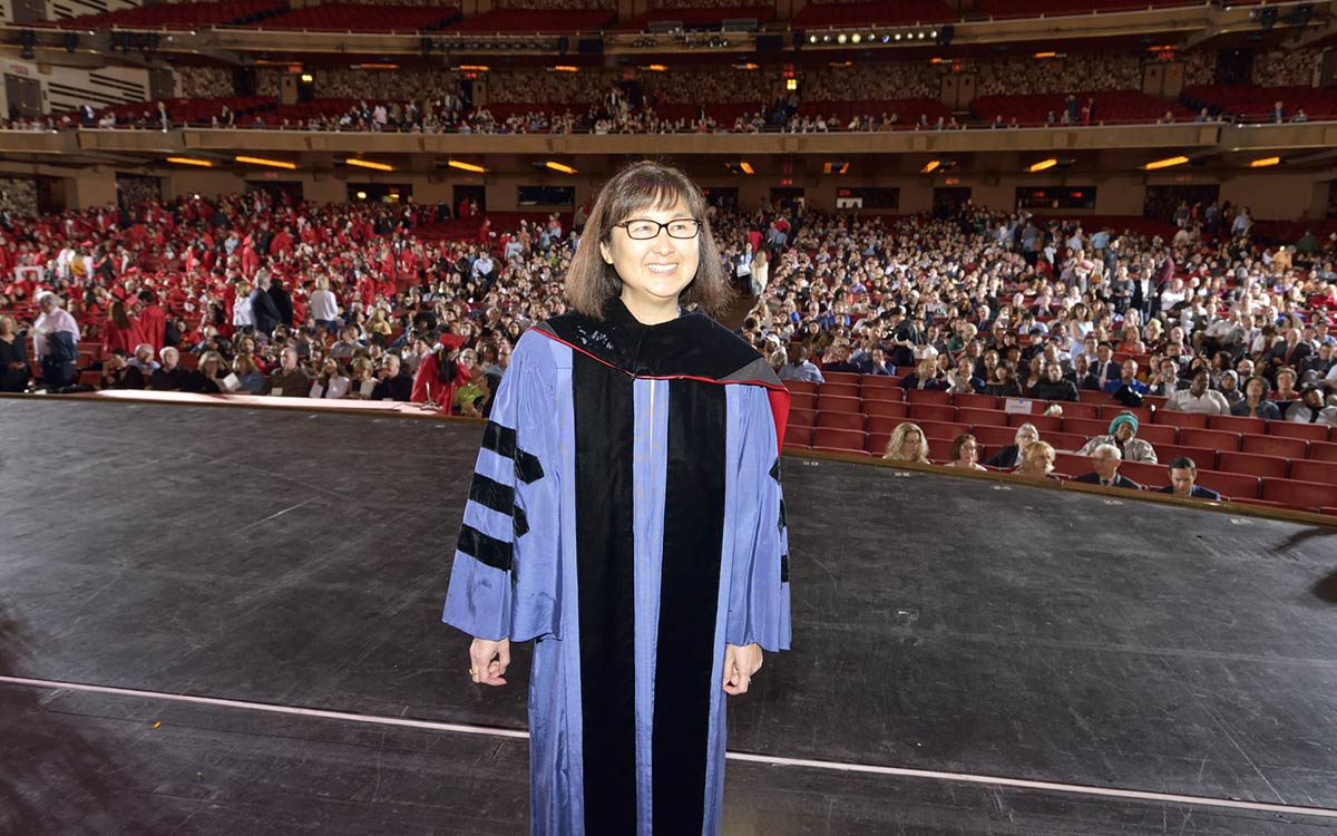 A masters graduate stands on stage in front of an audience.